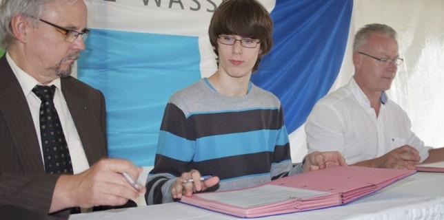Jens Dikow unterzeichnete (Bildmitte) unterzeichnete stellvertretend für die Schüler der Musikbetonten Gesamtschule Paul Dessau den Wassergenerationenvertrag. Links im Bild Rainer Werber, Geschäftsführer der DNWAB und