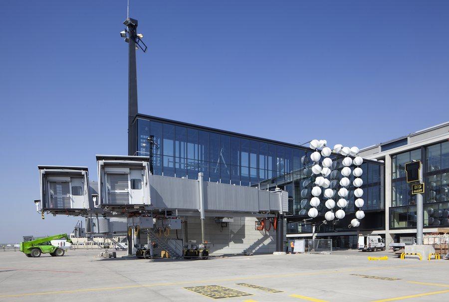 Im Juni installierte der Berliner Künstler Olaf Nicolai an der Fluggastbrücke des A380 ein riesiges Kunstwerk, das die Brücke wie Perlen schmückt. (Foto: Flughafen Berlin-Brandenburg, Alexander Obst / Marion Schmieding)