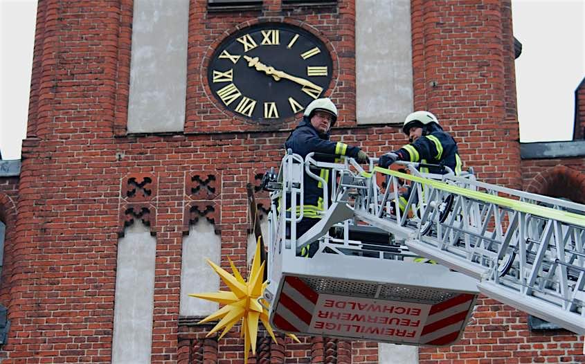 Für die Feuerwehr Eichwalde ist es eine Arbeit von wenigen Minuten, den Adventsstern am Kirchturm der evangelischen Kirche zu installieren. (Foto: Burkhard Fritz)