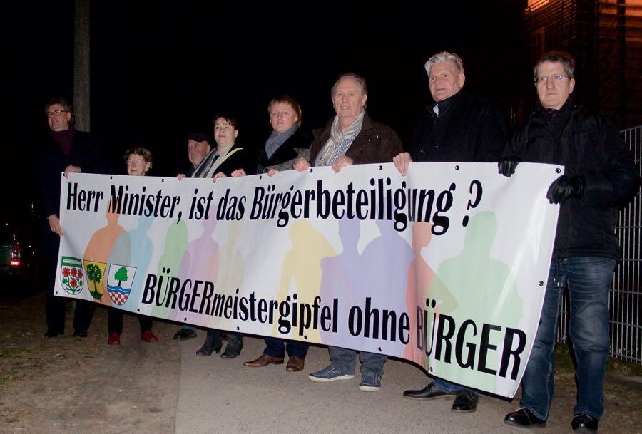 Gemeindevertreter aus Schulzendorf und Zeuthen empfingen Innenminister Schröter mit einem Protestbanner über die Abwesenheit von Bürgerbeteiligung. (Foto: Jörg Levermann)