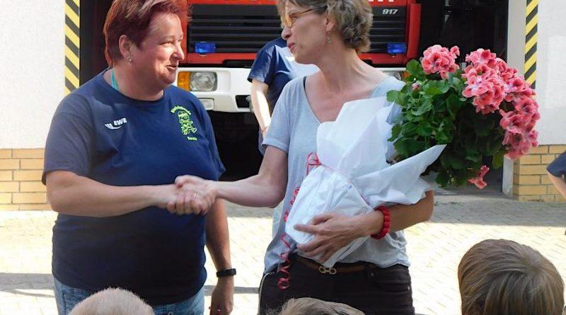 Tina Fischer (rechts) bedankt sich mit einem Blumenstrauß bei Feuerwehrfrau Kerstin Schildberg für ihre Arbeit mit dem jüngsten Feuerwehrnachwuchs. (Foto: Christian Könning, Landtagsbüro Tina Fischer)